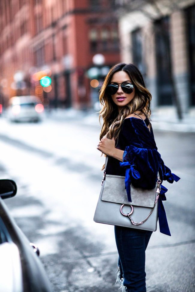 fashion blogger mia mia mine wearing a blue velvet top with ribbons and a chloe faye bag