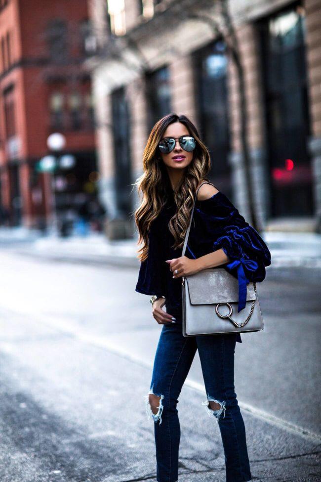 fashion blogger mia mia mine wearing a blue velvet top and chloe faye bag