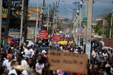 Protesters march to the embassy of the Dominican Republic in Port-au-Prince, Haiti, Wednesday, Feb. 25, 2015. The protesters are outraged over a Feb. 11 lynching of young man of Haitian descent in the Dominican city of Santiago and are demanding that the neighboring country respect the human rights of Haitians.