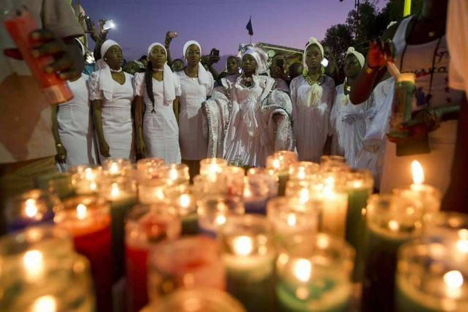 Haitian women look on near a memorial at the site of an accident during a march convened by the government in Port-au-Prince on February 17, 2015, in memory of the victims who died during celebrations in the National Carnival of Haiti. Haiti was plunged into mourning and Carnival festivities were cancelled after at least 16 people died when a high-voltage cable hit a parade float in the capital Port-au-Prince.