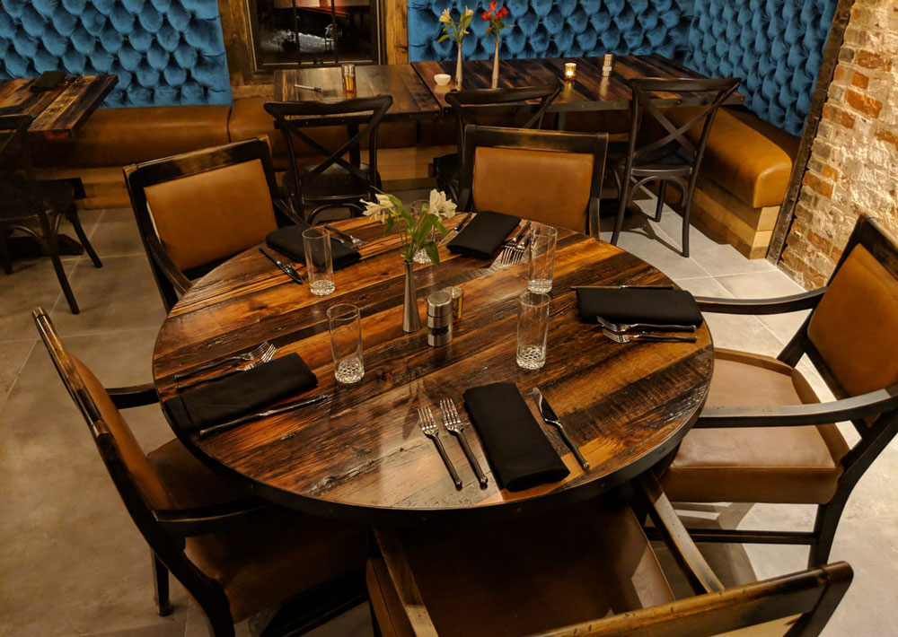 Barnwood and steel tables, and custom banquettes with diamond tufting at the Beehive Augusta Tavern by Michael Colemire