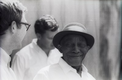Mississippi John Hurt with Doc Watson in background, 1964 Berkeley Folk Music Festival. Photographer unknown.