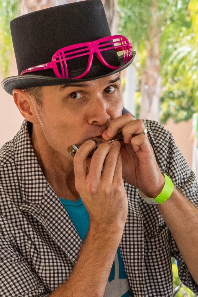 Michael Mahin in a black top hat with pink sunglasses in a checkered jacket playing the harmonica