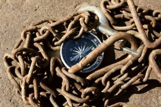 Compass in the Sand with An Old Chain