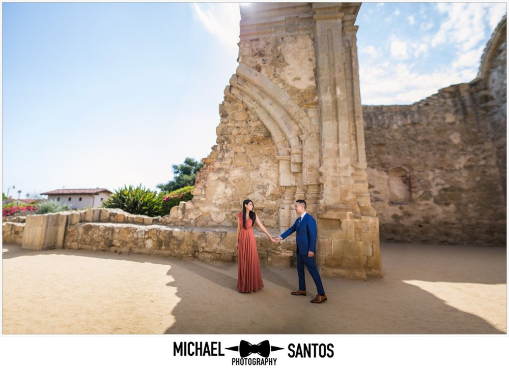 woman leading guy smiling at their mission san juan capistrano engagement session