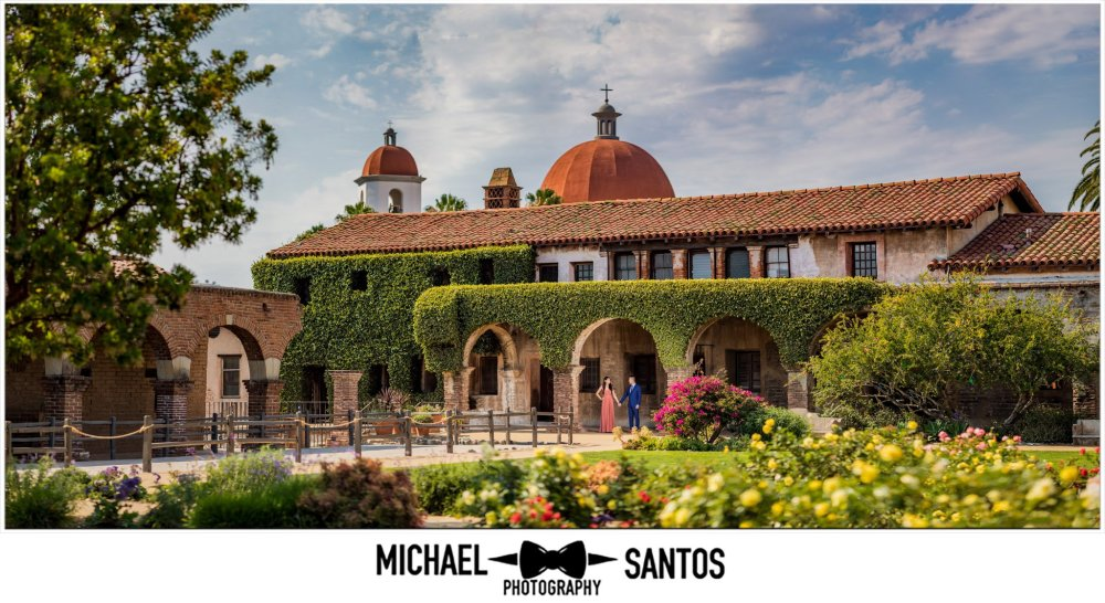 epic wide shot with couple showing the dome for this mission san juan capistrano engagement session