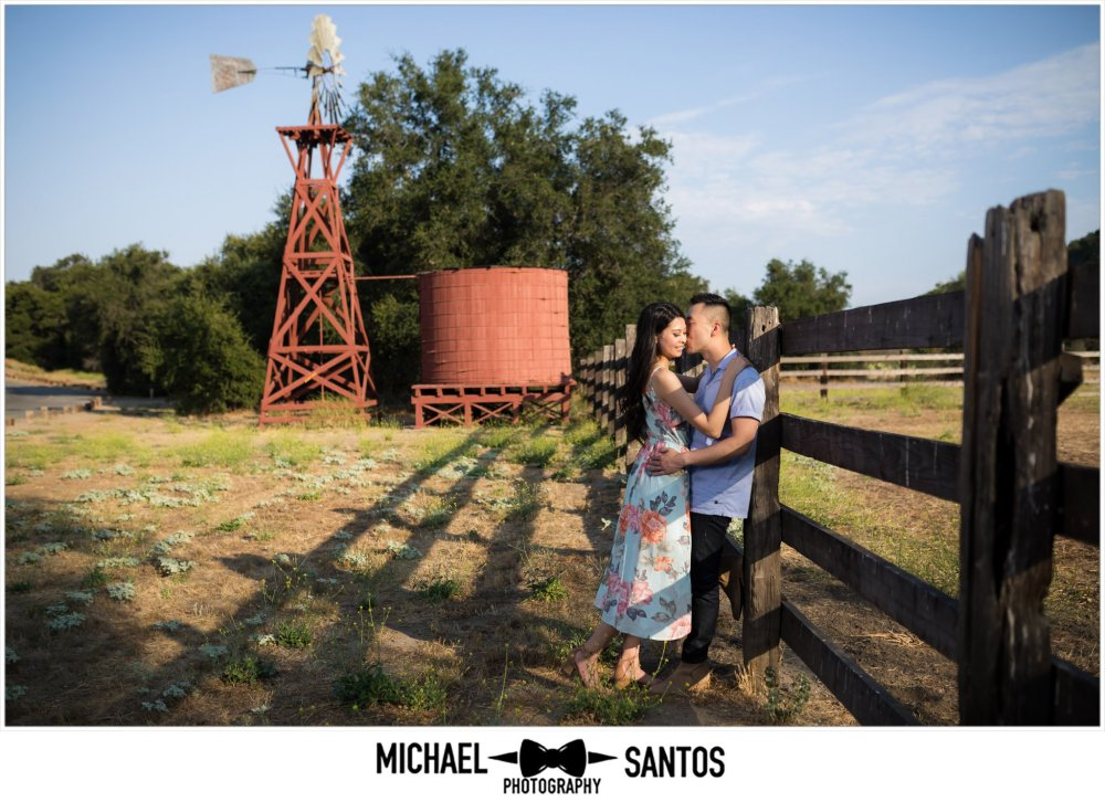 couple hugging against the fence during their caspers wilderness park engagement photography session
