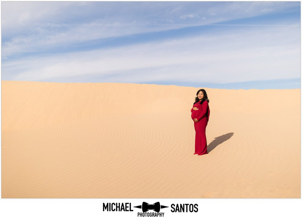 expecting mother in red dress standing in the sand dunes during her maternity session