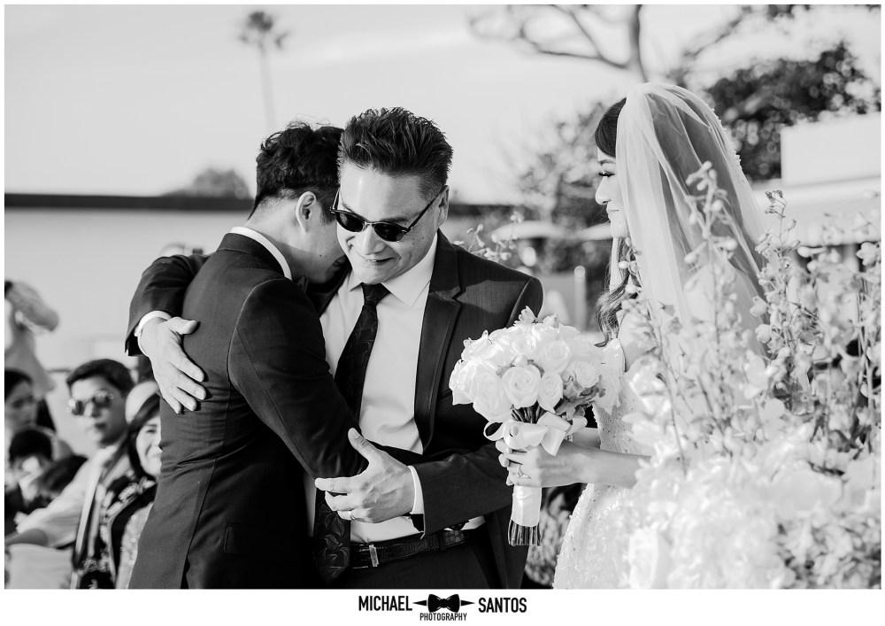 groom hugging father of bride at surf sand sand resort in laguna ca