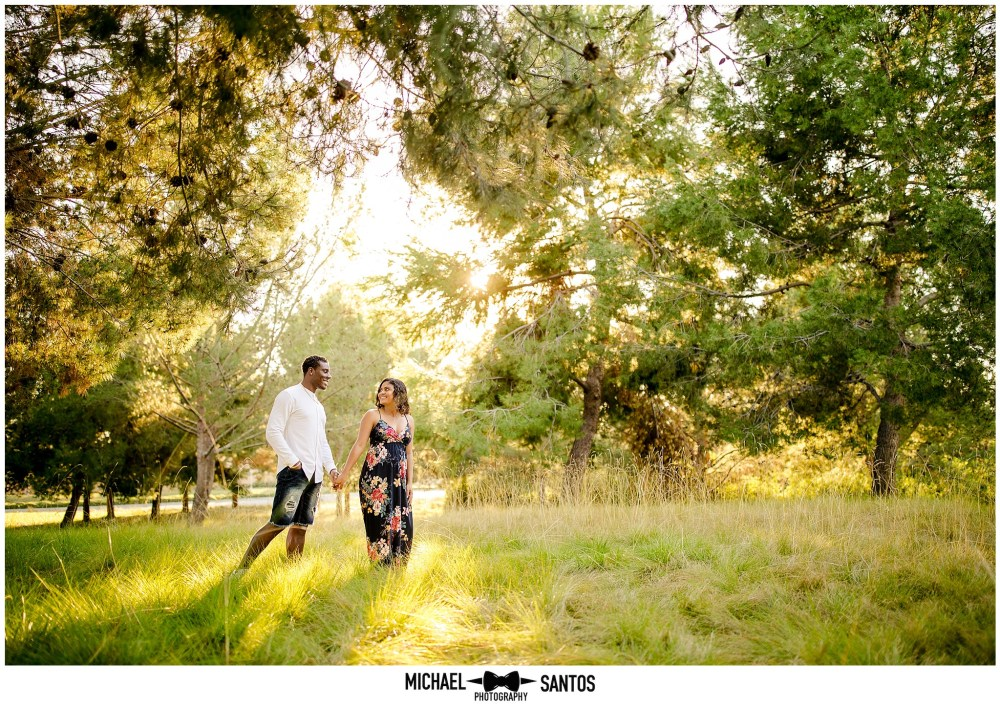 married couple walking through field during their baby announcement photo session