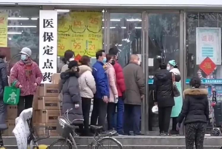Citizens of Wuhan China standing in line outside a drug store during 2020 coronavirus outbreak.