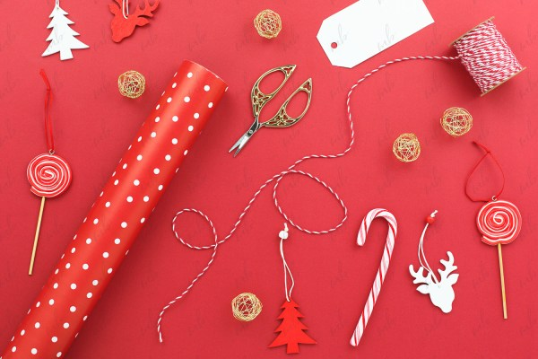 Christmas Styled Stock Photo - wrapping paper, tags, decorations on red background