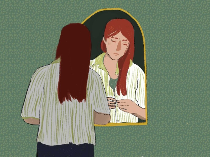 Girl looking into mirror and buttoning her shirt