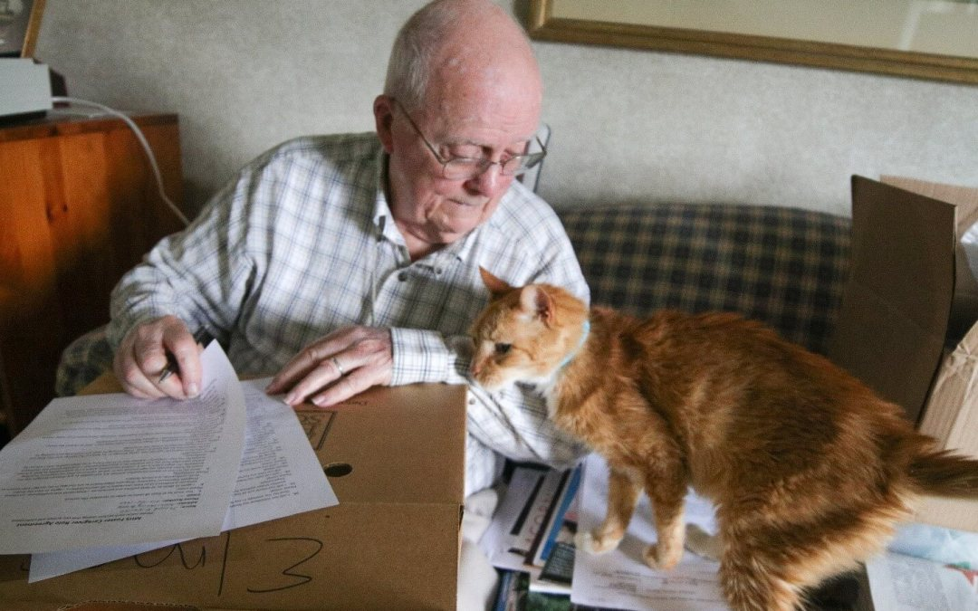 A senior citizen with his cat.