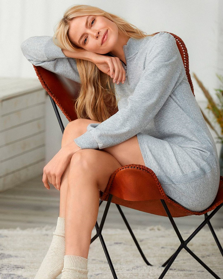 A women sitted in a chair with a comfy gray dress, she looks happy
