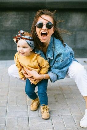 Madre e hija bebé miran a cámara y sonríen, ella leva ropa de mujer de segunda mano
