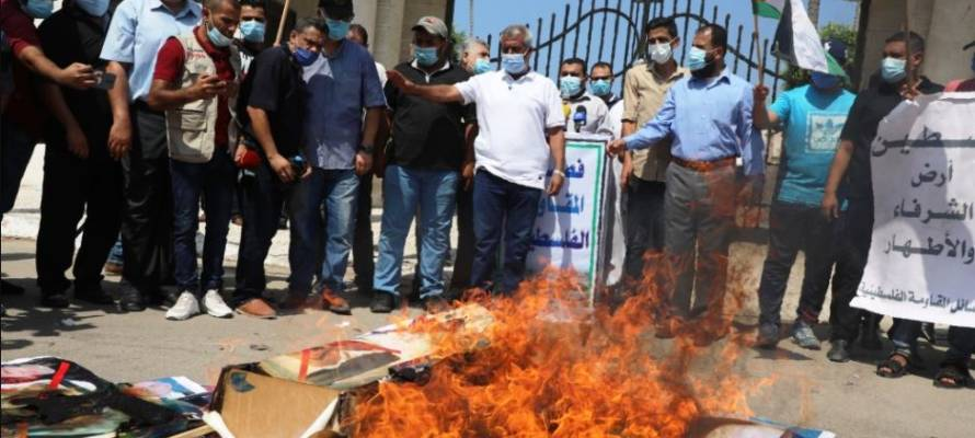 Palestinians burn pictures of President Trump, the Bahraini monarch, Abu Dhabi's Crown Prince, and PM Netanyahu in Gaza City, Sept. 15, 2020. (Majdi Fathi/TPS)