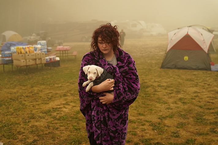 Shayanne Summers holds her dog Toph while wrapped in a blanket after several days of staying in a tent at an evacuation center at the Milwaukie-Portland Elks Lodge in Oak Grove, Oregon. (AP Photo/John Locher)