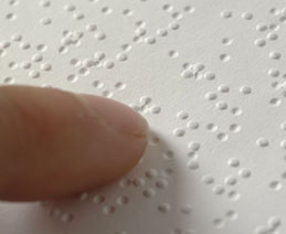 Closeup of finger on Braille text