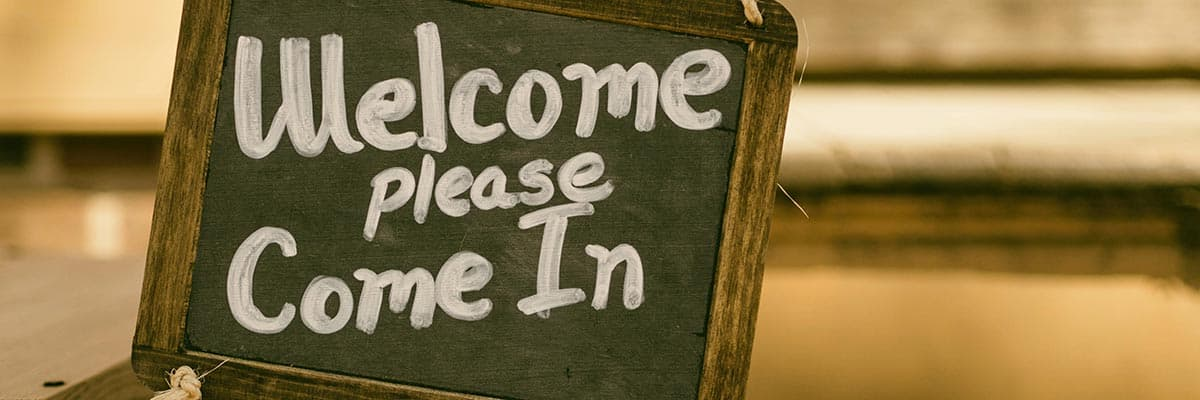 "Chalkboard sign with ""Welcome, Please Come In."" Advocates remind readers that customer service is one form of disability inclusion."