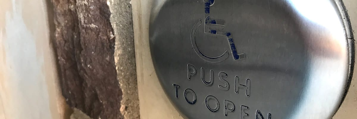"""Automatic door opener button at building entrance, with """"Push to Open"""" and International Symbol of Access."""