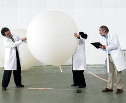 Three scientists measure very large balloon in laboratory setting.