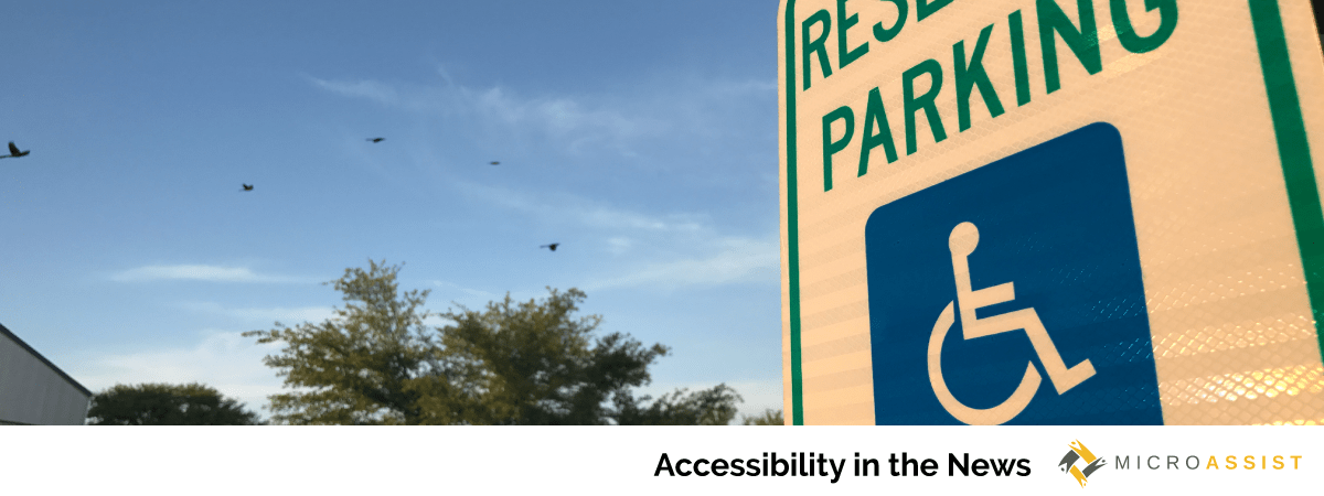 """A """"reserved parking"""" sign with the international symbol of access stands in the foreground against a background of trees and bright blue skies."""