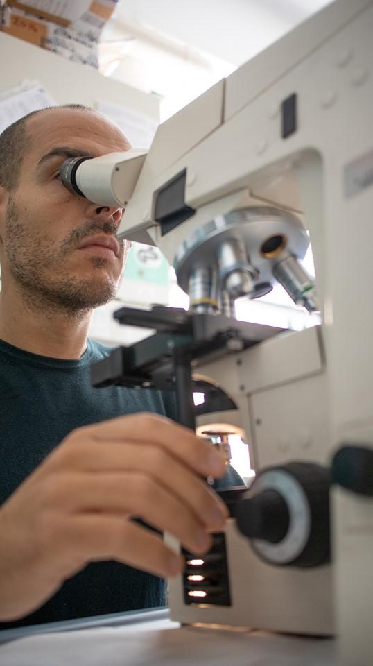 Alessandro Mustazzolu alle prese con un microscopio ottico