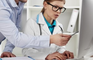 An employee teaching a physician how to use an EHR system