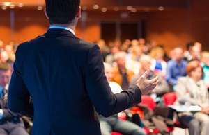 A professional presenting in front of a crowd of people at a vendor conference