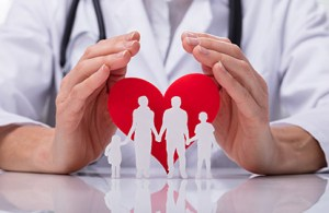 A hand holding a heart with a family inside to represent caring and mitigating physician burnout.