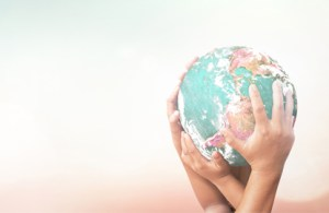Globe held in hands symbolizing population health commitment.
