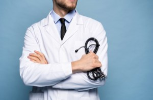 confident doctor stands with arms crossed holding a stethoscope