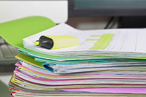 stack of folders paperwork and highlighter