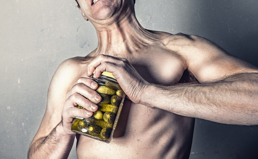 A Man shirtless struggling to open a jar