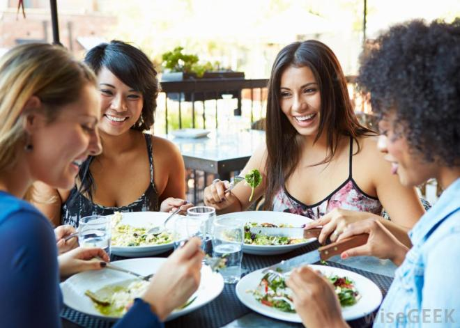 Women eating salads and laughing at a outdoor patio restaurant. Photo is courtesy of WiseGeek