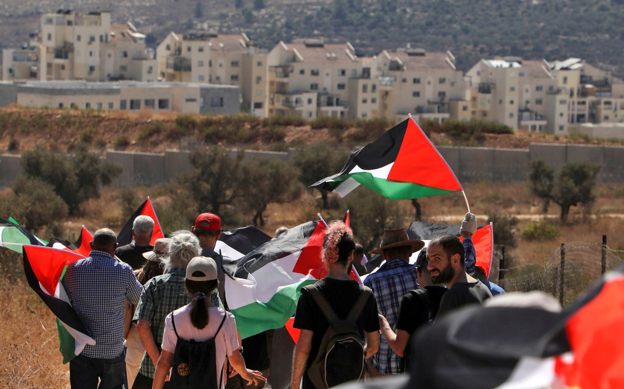 Palestinian and foreign demonstrators in Bilin opposite the settlements bloc of Modiin Illit (background) in the occupied West Bank on 4 October