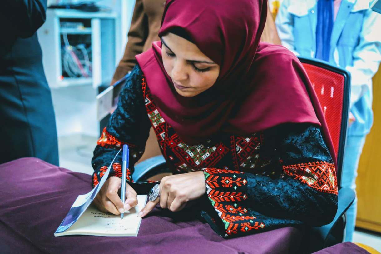 Shurooq Doghmosh signing copies of her debut novel, 'I Was Killed At Around This time' (Facebook)