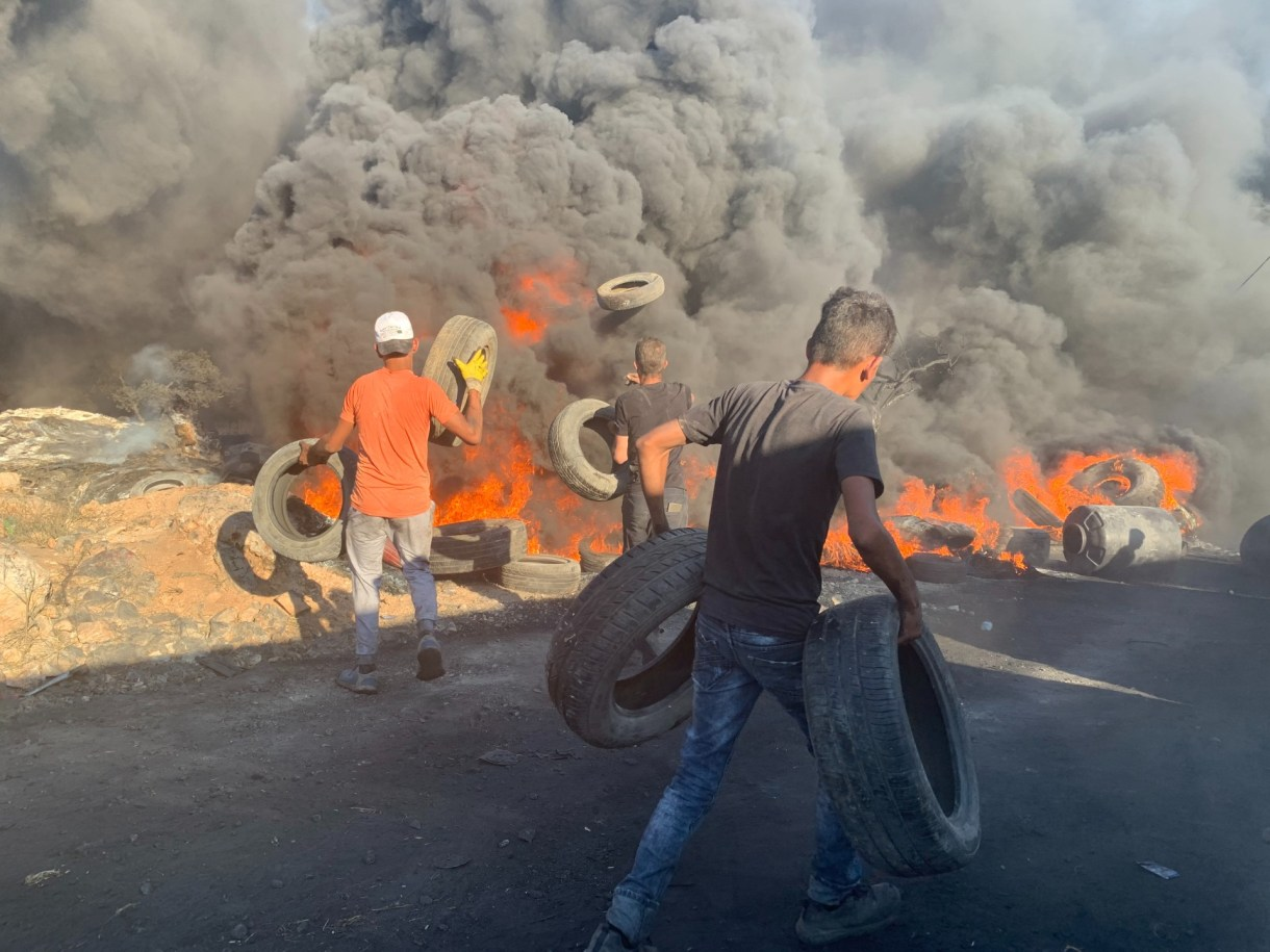 Palestinian youths set fire to tyres during a protest against an illegal Israeli settlement outpost in Beita (MEE/Shatha Hammad)
