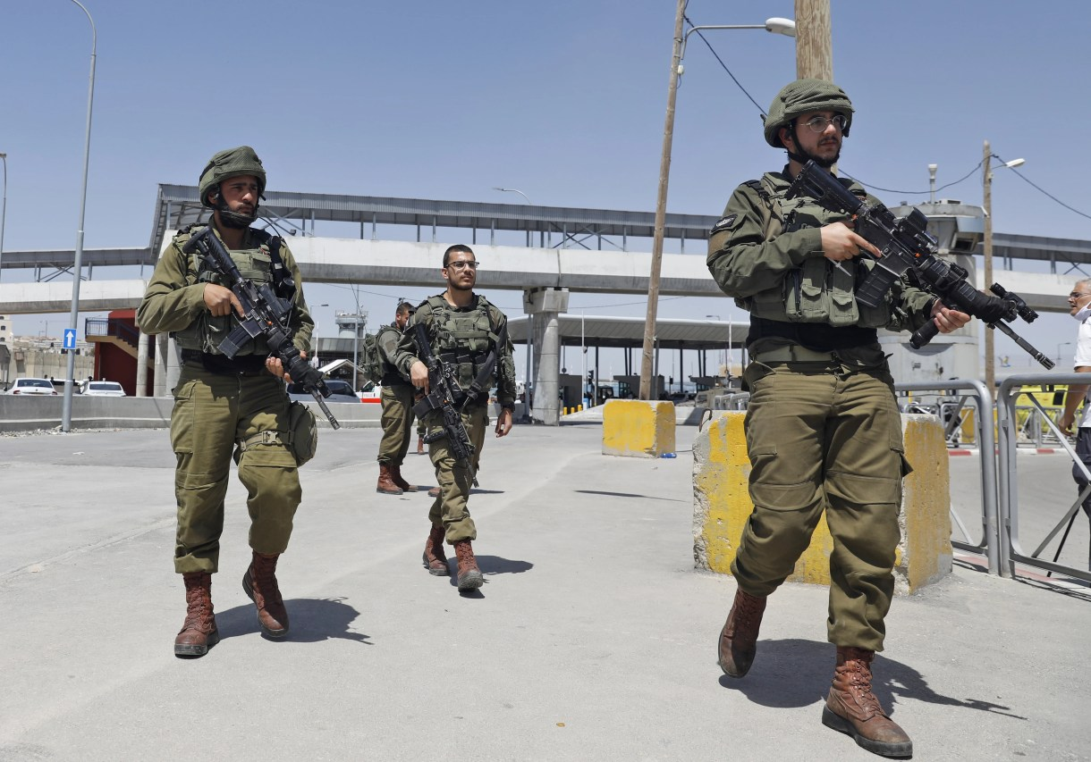 Israeli soldiers gather at the Qalandiya checkpoint in the occupied West Bank on 12 May (AFP)