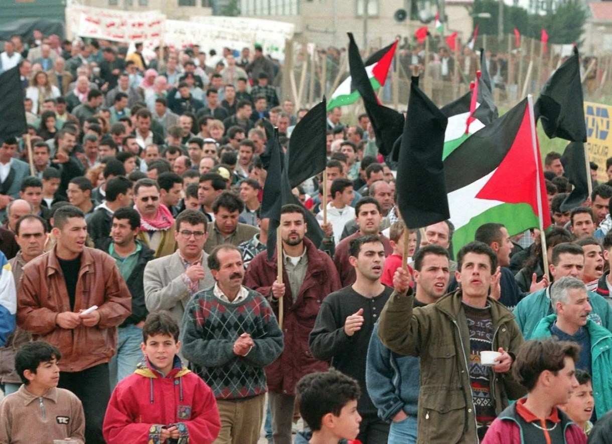 Palestinians holding black and Palestinian flags march 30 March 1998 in Sakhnin on the anniversary of the killing here in 1976 of six Israeli Palestinians protesting land confiscations by Israel (AFP)