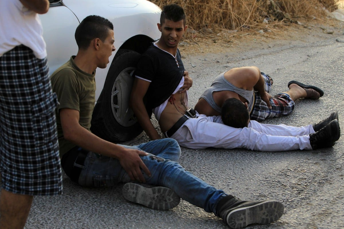 Palestinian demonstrators lay on the ground after being reportedly shot by Israeli soldiers in a street, east of the West Bank city of Nablus, on October 3, 2015, during a search for the suspected killers of a Jewish settler couple. [JAAFAR ASHTIYEH/AFP via Getty Images]