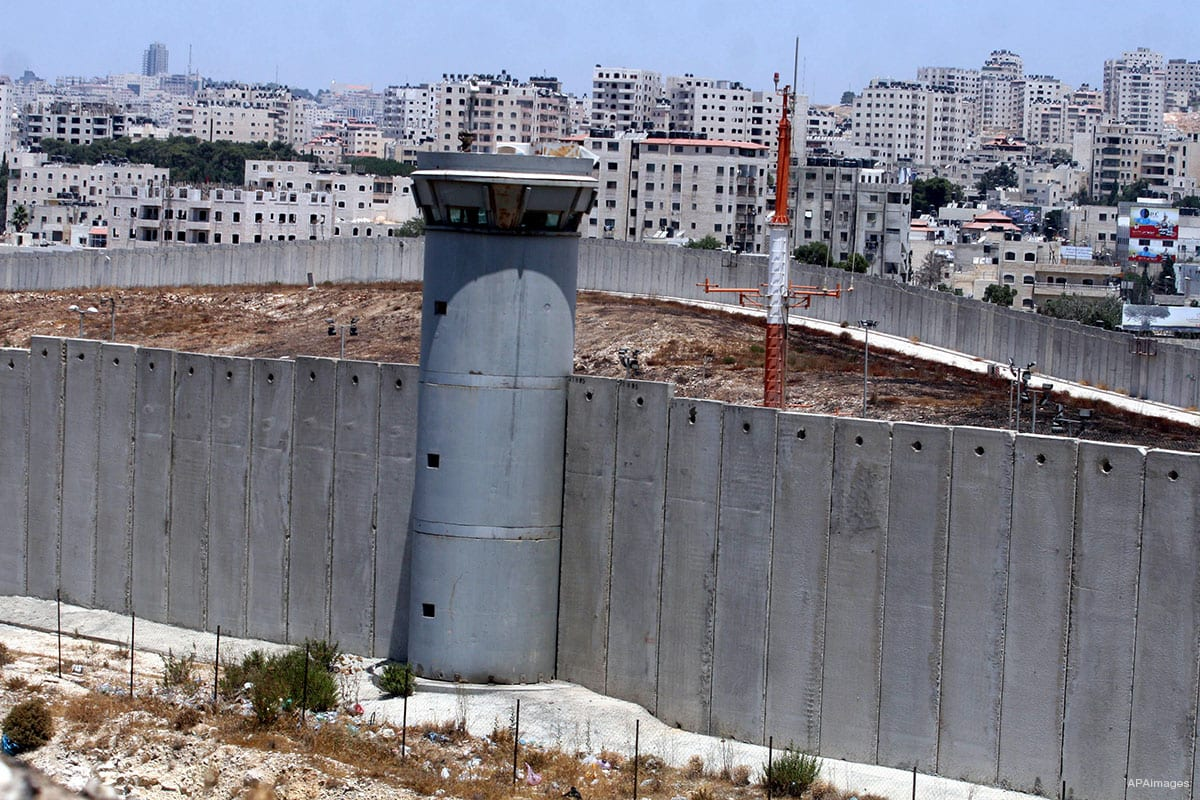 Image of the apartheid wall in West Bank and an Israeli military watchtower [Apaimages]