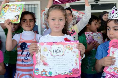Syrian students living in refugee camps in Turkey receive their end of year school certificates [Anadolu]