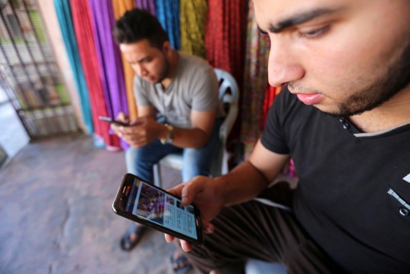Image of youths on their phones [Reuters/Ibraheem Abu Mustafa]