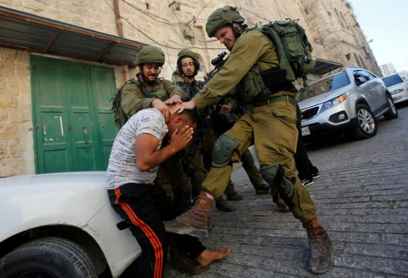 Israeli soldiers detain a Palestinian during a searching raid by Israeli troops, in the West Bank [REUTERS/Mussa Qawasma]