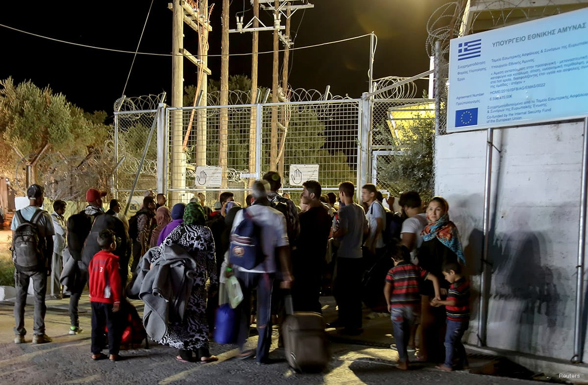 Refugees and migrants stand at the closed gate of the Moria migrant camp in Greece on September 19, 2016 [Intimenews/Manolis Lagoutaris/via REUTERS]