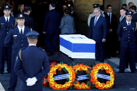 Israeli Prime Minister Benjamin Netanyahu (C) stands next to the flag-draped coffin of former Israeli President Shimon Peres, as he lies in state at the Knesset plaza, the Israeli parliament, in Jerusalem September 29, 2016. REUTERS/Amir Cohen