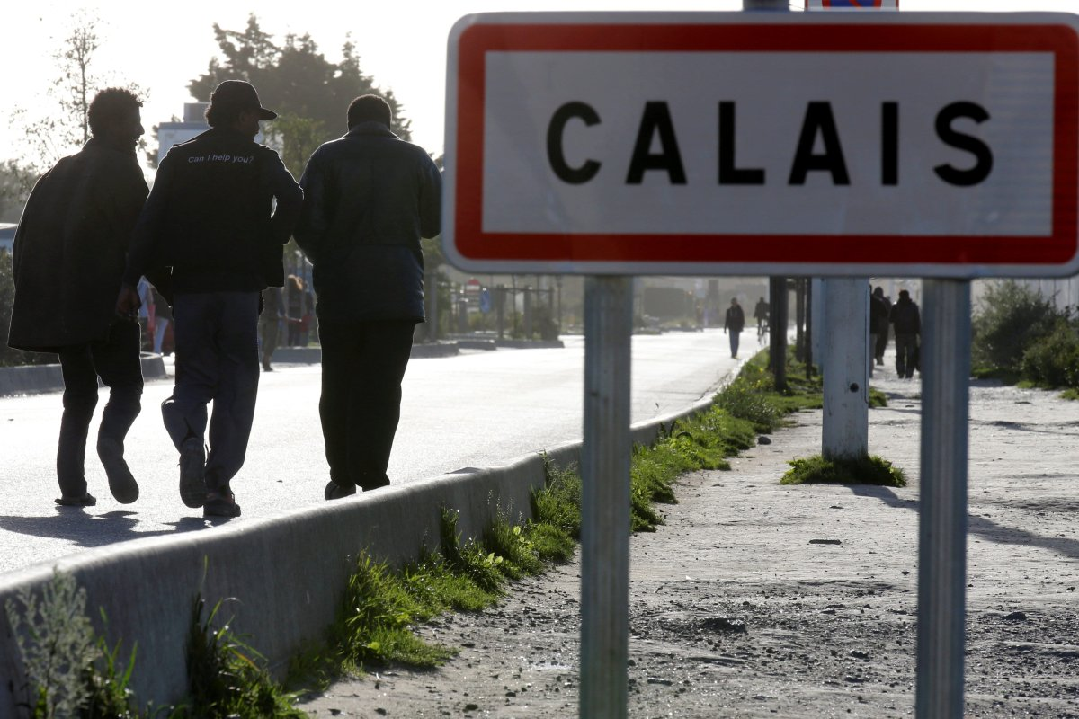 "Migrants pass by a road sign as they leave the northern area of the camp called the ""Jungle"" in Calais, France, 25 September 2016. [REUTERS/Pascal Rossignol]"
