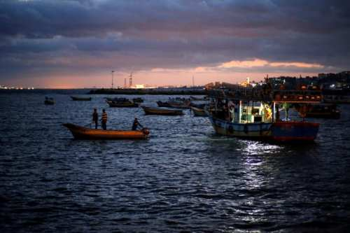 Palestinian fishermen ride their boats as they return from fishing at the seaport of Gaza City early morning 26 September 2016. [REUTERS/Mohammed Salem]